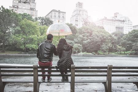 uomo sotto la pioggia: L'amore e la pioggia. Coppia seduta su una panchina nel parco centrale, New York durante una giornata di pioggia