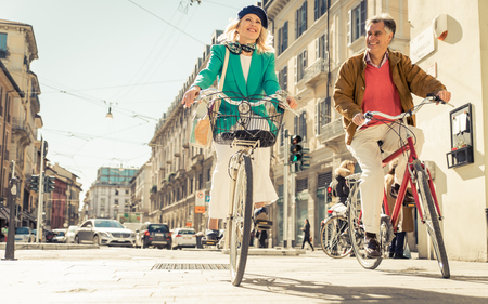 woman middle age: Senior couple riding their bicycle in the city center