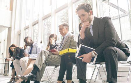 Ряд деловых людей, которые ждут интервью. Понятие о бизнесе и профессий