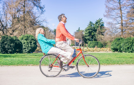 Happy senior couple riding on one bicycle in a park - Two peoplein the 60's having fun outdoors Standard-Bild
