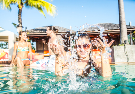 Portraitt of young attractive woman splashing water in a swimming pool - Group of friends having party in a pool Stock Photo