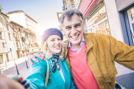 old technology: Senior couple taking selfie outdoors - Happy mature pair having fun while walking on the streets outdoors