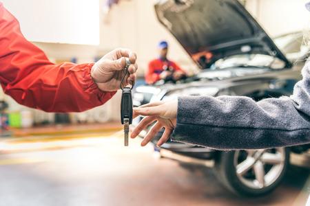 Автомобиль мастерская, женщина поднимая ее автомобиль - Механик рабочий на двигатель автомобиля, женщина, давая автомобиль ключ для проверки вверх