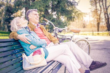 mujer sentada: alegre pareja de ancianos sentados en un banco en un parque - Dos jubilados que se divierten juntos al aire libre