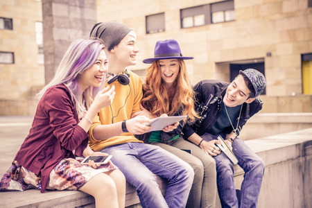 hilarity: Multiracial group of best friends laughing and having fun outdoors - Multiethnic  young teenagers looking down at computer tablet