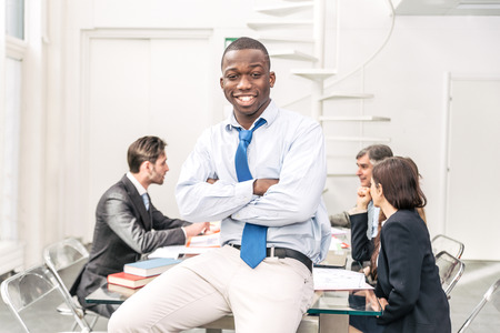 african american woman business: Afroamerican business man portrait - Team of businessmen in a conference meeting, confident young man smiling at camera with crossed arms Stock Photo