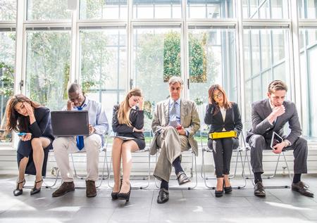 Wielorasowe grupa ludzi biznesu siedzi w poczekalni podczas upadłości spółki - przygnębiony i zmęczony zespół przedsiębiorców czeka na rozmowę kwalifikacyjną