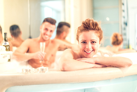 wife of bath: Couple of lovers relaxing in a jacuzzi full of foam - Partners celebrating anniversary in a luxury spa resort