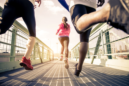 training shoes: Three runners sprinting outdoors - Sportive people training in a urban area, healthy lifestyle and sport concepts Stock Photo