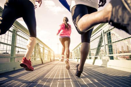 lifestyle: Tre corridori Sprint all'aperto - Gente allegra di formazione in una zona urbana, stile di vita sano e concetti di sport