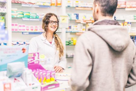 Фармацевт разговаривает с клиентом в аптеке столе