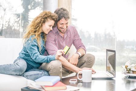 陽気なカップルは、クレジット カードを保持している女性、ソファでリラックスしながらコンピューターで探して
