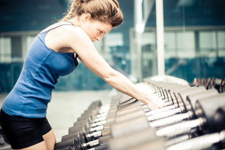 weight room: Sportive woman grabbing two dumbbells for a power workout session - Female athlete training in a weight room