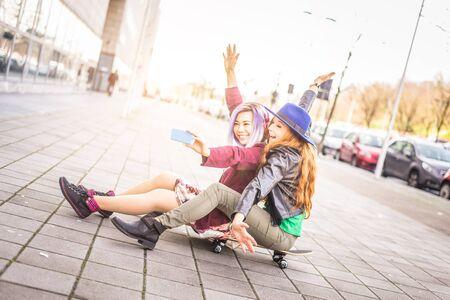 best friend: Two female best friends taking selfie outdoors - Cheerful girlfriends having fun