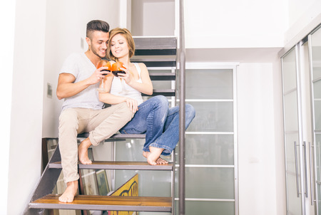 domestic life: Couple of lovers sitting on a staircase and toasting wine glasses to celebrate anniversay - Domestic life, partners relaxing at home Stock Photo