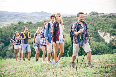 Group of hikers walking in the nature - Friends taking an excursion on a mountain, walking in a row