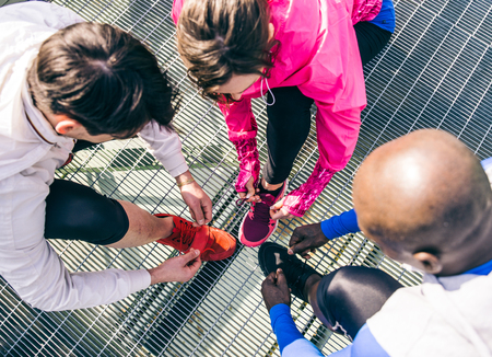 lacing sneakers: Multiethnic group of runners getting ready for a workout session - Athletes tying shoelaces and resting after a run outdoors