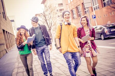 Groep jonge studenten wandelen buitenshuis in een universiteitscampus