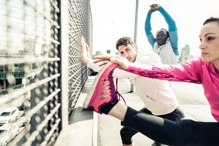 personas corriendo: Tres corredores deportivos multiétnicos de estiramiento y en reposo durante una sesión de entrenamiento en un área urbana Foto de archivo