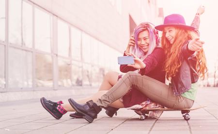 Two teen girls taking selfie sitting on a skateboard Stock Photo