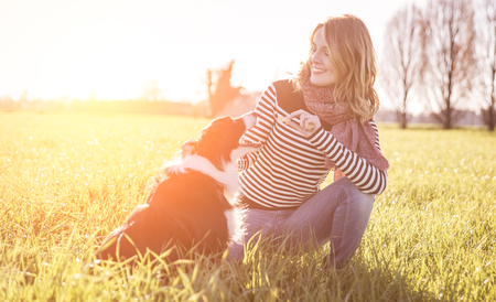 border collie: Smiling lady taking free time with her dog.Woman  relaxing in the nature with her loyal dog
