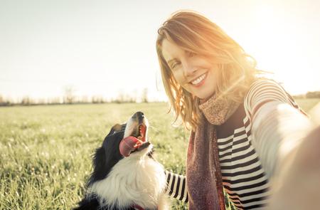 Lächelnde Dame, die selfie mit ihrem Hund. Frau und ihre treuen Border-Collie Hund