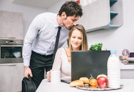 při pohledu na fotoaparát: Manžela líbat na rozloučenou se svou ženou před odchodem do práce Reklamní fotografie