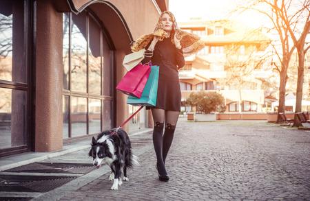 Modieuze vrouw en haar border collie hond die het winkelen in het centrum van de stad