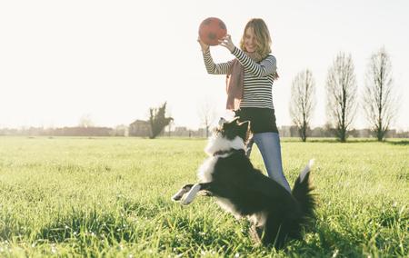 Sorridente signora prendendo il tempo libero con la sua dog.Woman relax nella natura con il suo cane fedele Archivio Fotografico