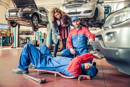 car shop: Two mechanics fixing a car and speaking with the customer in a workshop - Car at the annual test check-up