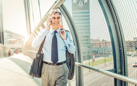 hombres maduros: Senior empresario caminar y tener una conversación en el teléfono - Retrato de hombre maduro confianza sonriente uso de traje elegante