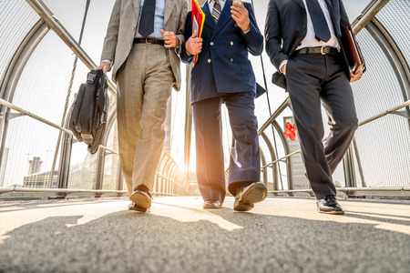 brak: Three businessmen walking in a financial area while having a conversation - Work colleagues going to work Stock Photo