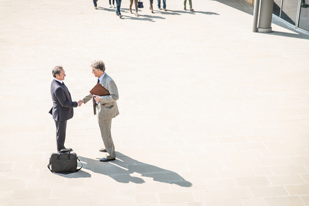 Two mature businessmen shaking hands outdoors - Managers having a deal after a conference meeting
