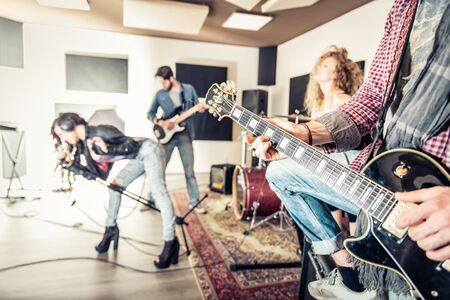 synthesiser: Rock band recording a music track in a studio - Friends performing music in a recording studio Stock Photo