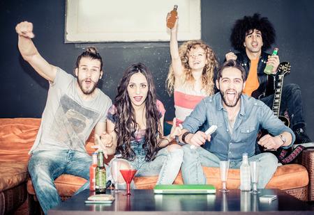 mujer viendo tv: Amigos alegres sentados en el sofá y exultante mientras ve un partido de deporte en la televisión - la gente fresca feliz y divertirse en una fiesta en casa
