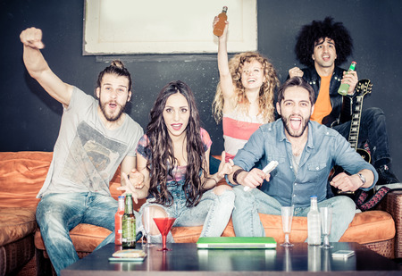 Cheerful friends sitting on the couch and exulting while watching a sport match on tv - Happy young cool people having fun at a home party Stock Photo