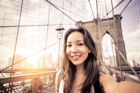 Довольно молодая женщина, принимая селфи на Бруклинский мост - Женский туристический осмотр достопримечательностей Нью-Йорк Фото со стока