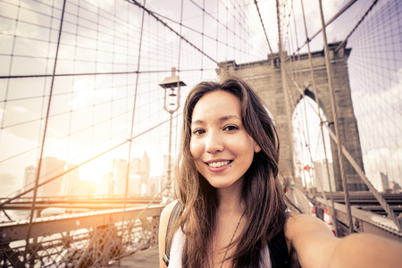 Pretty young woman taking a selfie on Brooklyn Bridge - Female tourist sightseeing New York Stock Photo