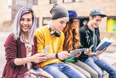 Gruppo multietnico di amici guardando al telefono e tablet, concetti sulla dipendenza della tecnologia e della gioventù