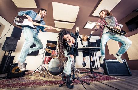 Woman beat guitar: Ban nhạc rock chơi hard rock trong studio. Khái niệm về giải trí và âm nhạc