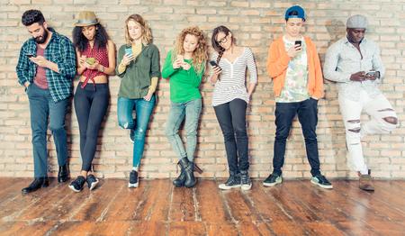Młodzi ludzie patrząc na telefon komórkowy - Nastolatki oparty o ścianę i SMS-y z ich smartfonów - pojęcia o technologii i globalnej komunikacji