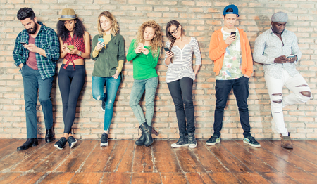 Young people looking down at cellular phone - Teenagers leaning on a wall and texting with their smartphones - Concepts about technology and global communication