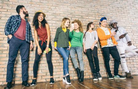 Los jóvenes mirando hacia abajo en el teléfono celular - Adolescentes apoyado en una pared y los mensajes de texto con sus teléfonos inteligentes - Conceptos acerca de la tecnología y la comunicación global Foto de archivo - 55653193