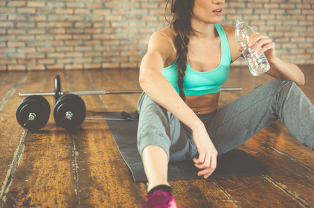 Woman drinking water after training on the sport mat Reklamní fotografie