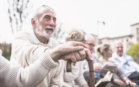 Gruppo di persone anziane fare attività all'aperto. Mani delle coppie su un bastone come concetto principale