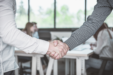 deal in: business deal and handshake. Business people with casual clothes in a start up office
