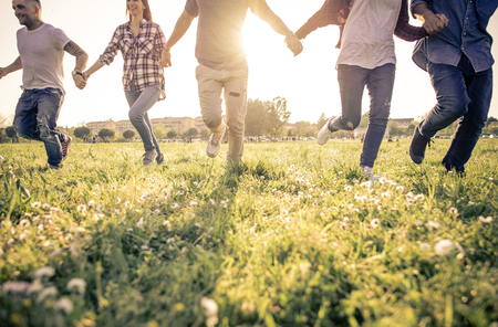Group of friends running happily together in the grass Stock Photo