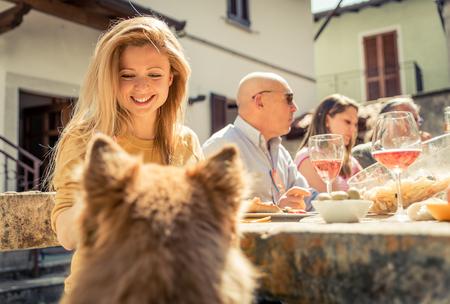 familias unidas: Grupo de amigos comiendo al aire libre. La mujer alimentando a su perro
