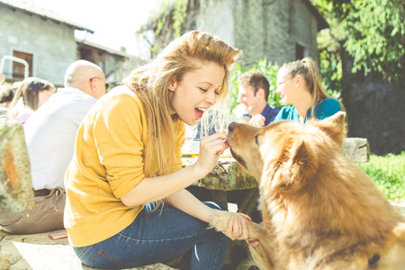 Group of friends eating outdoor. Woman feeding her dog