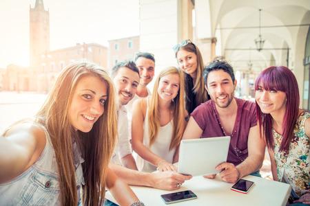 personas en la calle: Grupo de estudiantes que se sientan en un café bar y tomar una autofoto - amigos alegres jovenes que se divierten con la computadora portátil - Las personas activas viendo una película divertida en línea